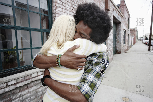 Couple hugging on sidewalk