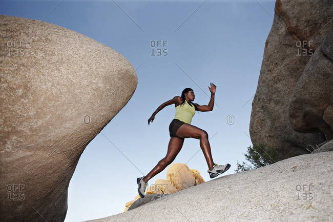 Woman running up boulder in remote area