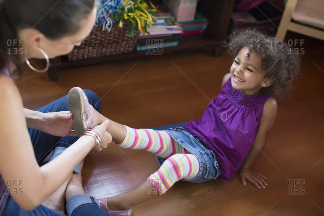 Mother putting shoes on daughter