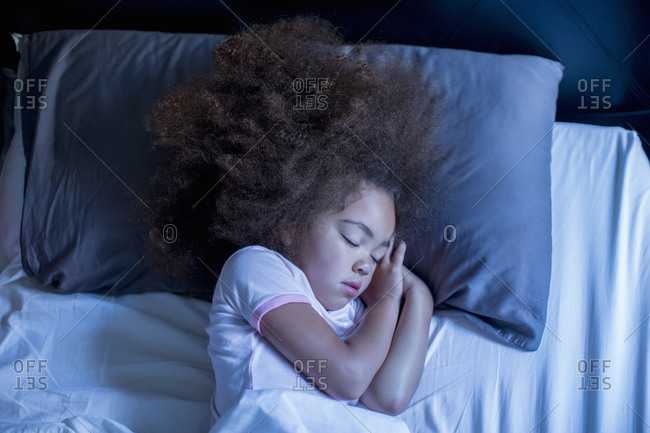 Mixed race girl sleeping in bed