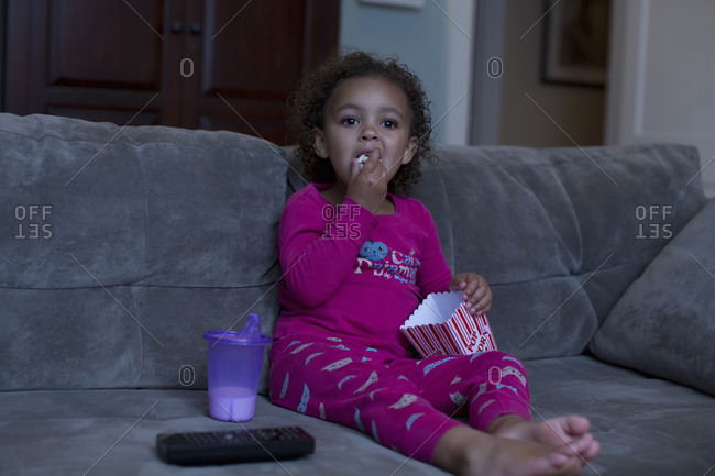 Mixed race girl eating popcorn and watching television