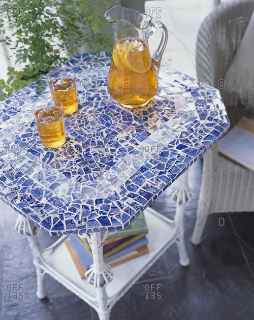 Glass pitcher and two glasses of ice tea standing on a mosaic table