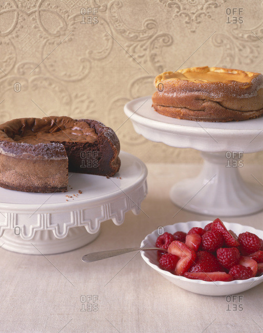 Two cakes served on cake stand with a bowl of fresh berries