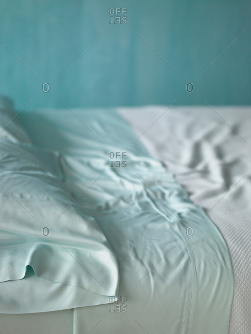 An unmade bed with crumpled sheet.