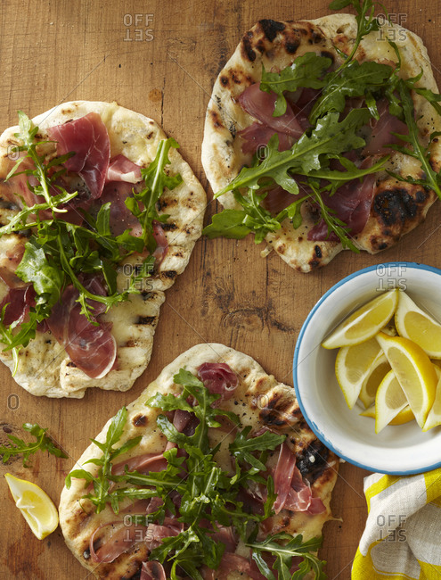 Baked flatbread with ham and arugula on top, from above.