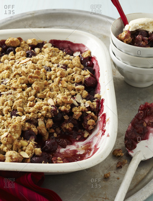 Cherry crumble dessert with nuts in white dish.