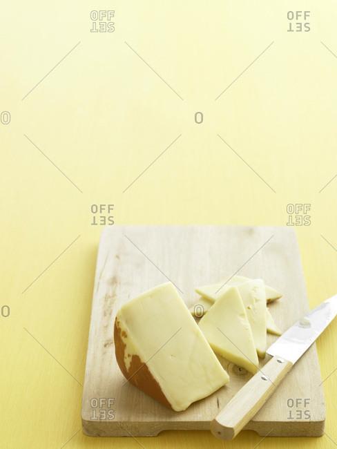 Semi-soft cheese on a chopping board.