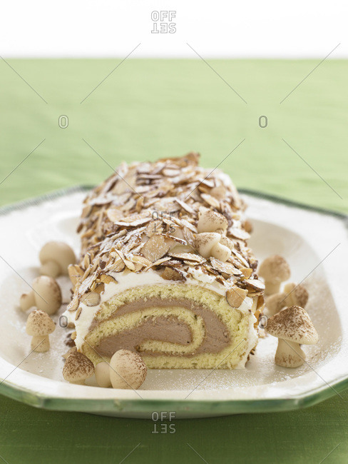 Chocolate buttercream roulade decorated with almond flakes and marzipan mushrooms.