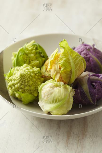 Orange, purple, white cauliflower and romanesco broccoli on a bowl.
