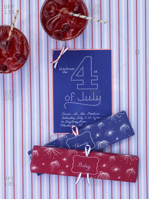 Invitation card for celebrating the 4th of July and raspberry juices from above.