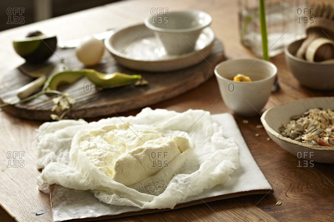 Homemade ricotta on cheesecloth, avocado, egg, flower in the background.