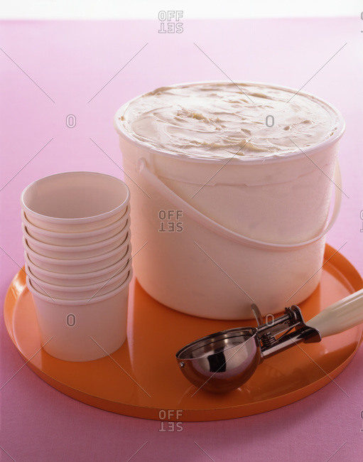 Bucket of vanilla ice cream with cups and serving scoop