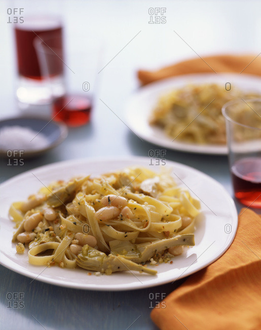Spaghetti with bean and artichoke, seasoned with chopped nuts.