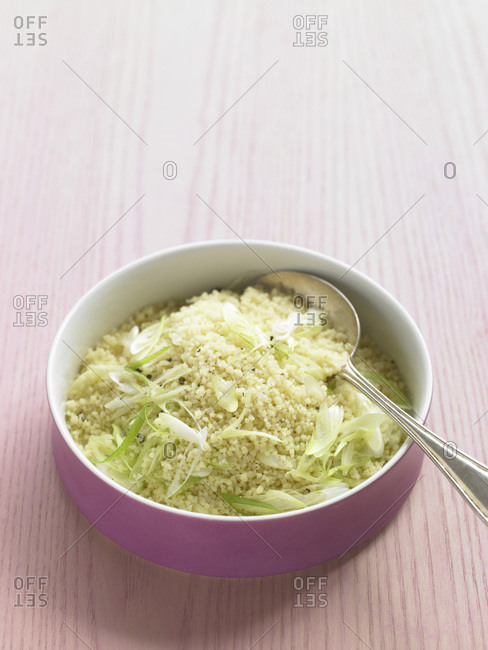 Pastina with spring onion in a pink bowl.