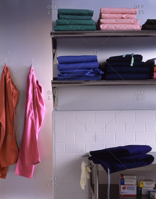 Colorful folded clothes on shelf.
