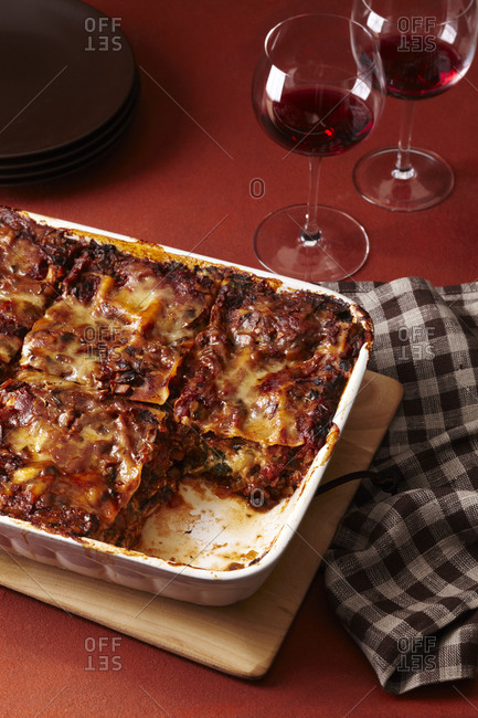 Lasagna with tomato and cheese in a white casserole dish.