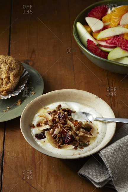 Bowl of yogurt and muesli with muffin and fruit salad