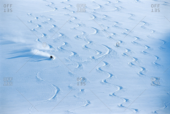 A person skiing in snow covered with skiing tracks