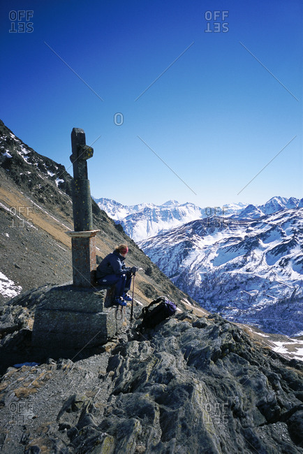 Man sitting on built structure in mountain