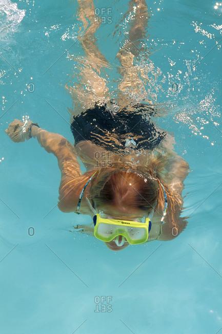 Girl wearing scuba mask swimming in pool