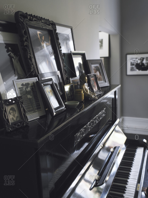 A collection of family photos placed on a piano