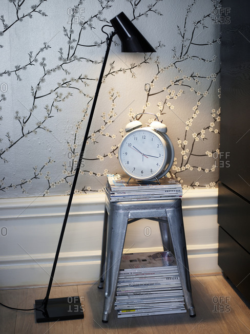 Stylish modern room design with lamp and alarm clock on top of silver painted stool