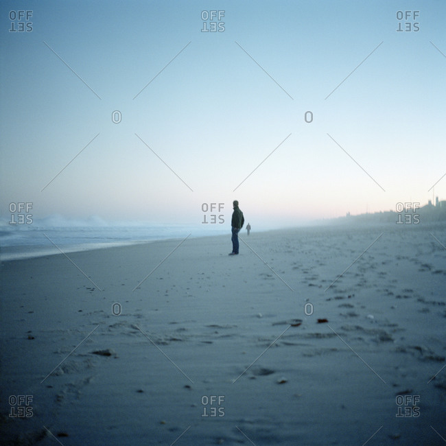 A man standing on a beach, New Jersey, USA