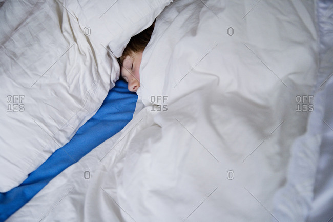 A sleeping boy between white and blue sheets, Sweden