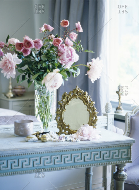 Antique mirror and flower vase on table