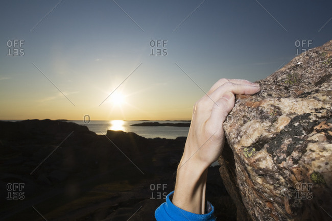 Scandinavia, Sweden, Bohuslan, Man climbing rock with sea in background