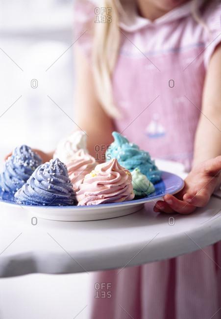Girl holding plate of meringue