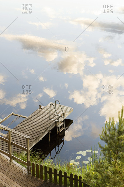 Jetty beside lake with reflection of sky