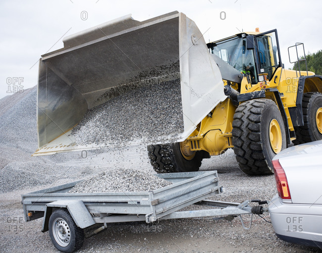 Gravel being poured by construction vehicle into container