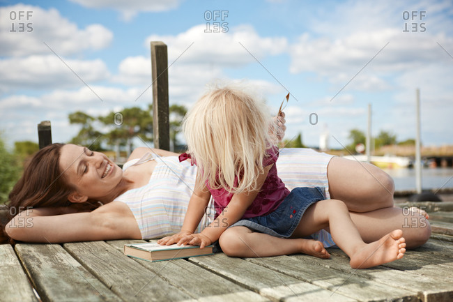 Mother and daughter resting on jetty