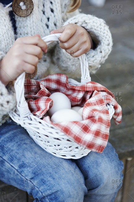 Girl holding eggs in basket
