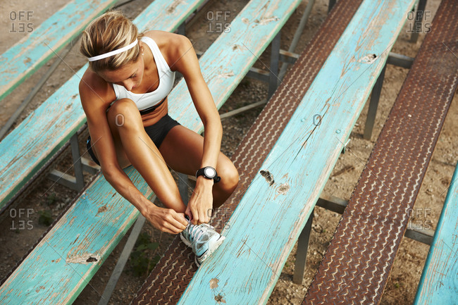 Female runner tying shoe