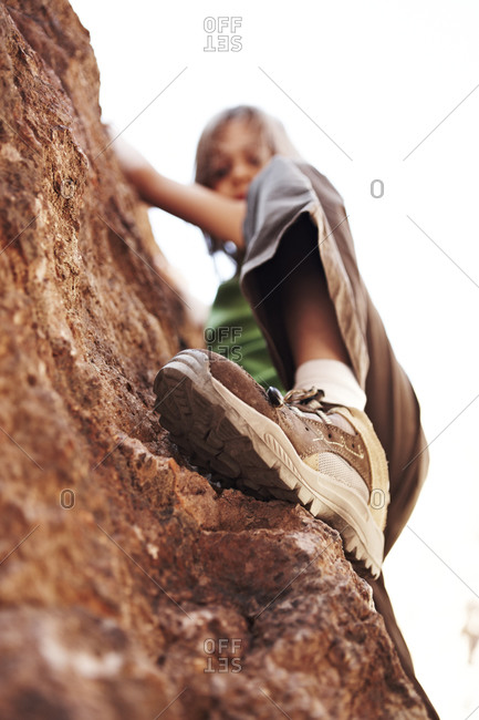 Low angle view of girl climbing rock