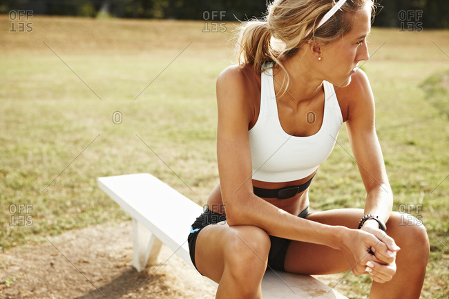 Female runner sitting on bench