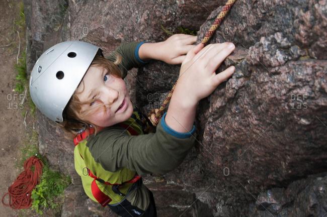 Boy climbing on rock