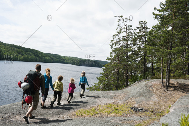Family with four children walking along lakeshore