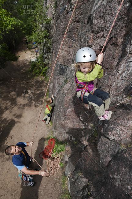 Father protecting climbing girl