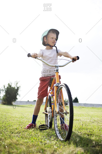 Boy on bicycle in field bicycle