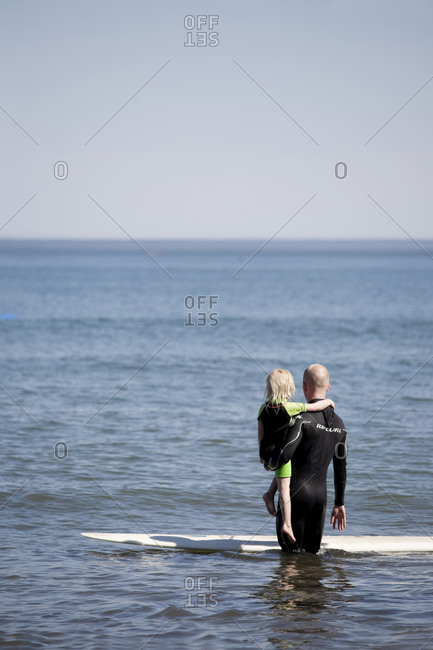 Daughter and father standing in sea