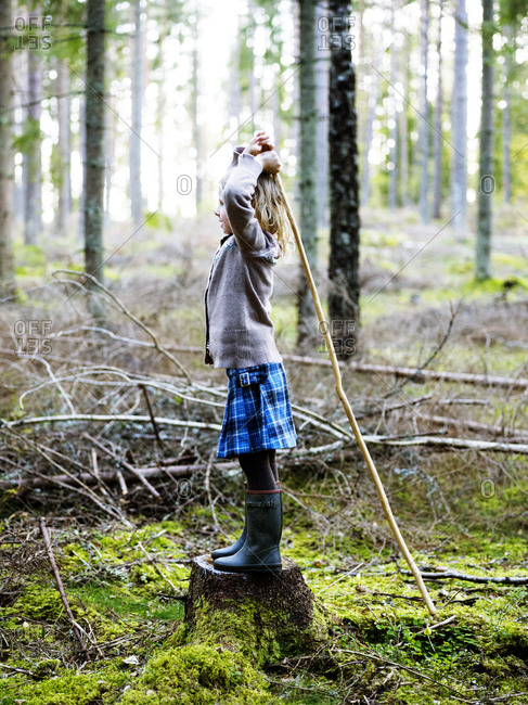 Girl standing on tree stump and holding stick amusement