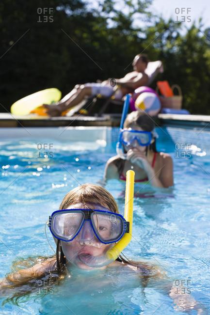 Children in scuba masks swimming in swimming pool
