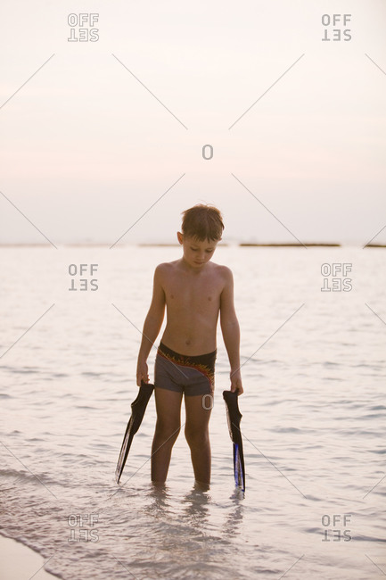 A boy with diving flippers by the sea at sunset