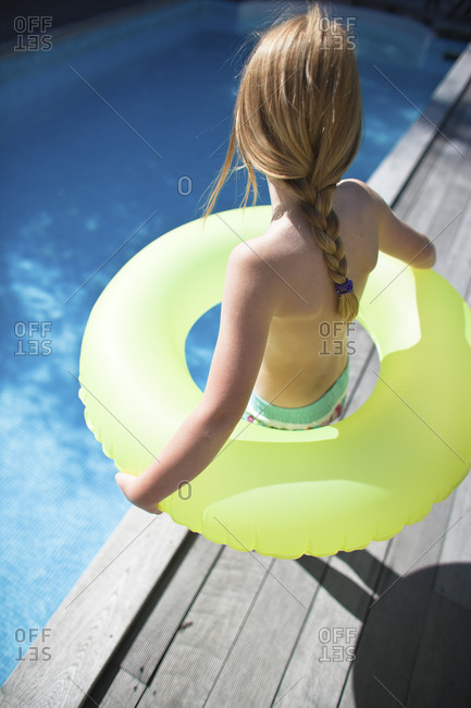 Daughter holding inflatable ring on the edge of swimming pool