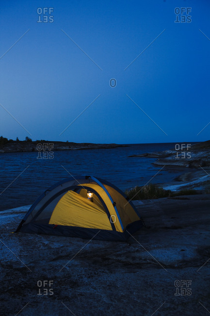 Illuminated tent by sea at dusk