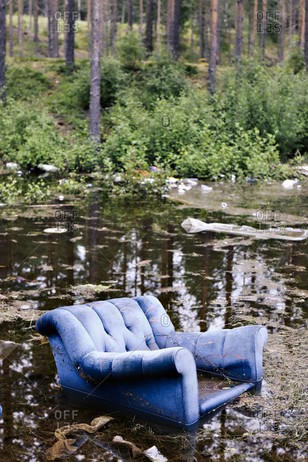 Old armchair in lake in forest abandoned