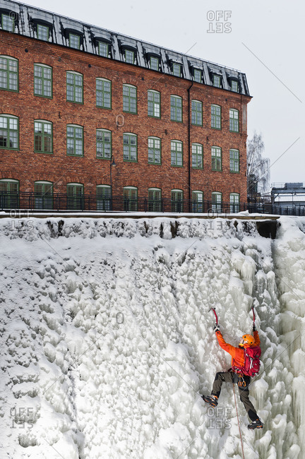 Man ice climbing up frozen waterfall in urban area adventure
